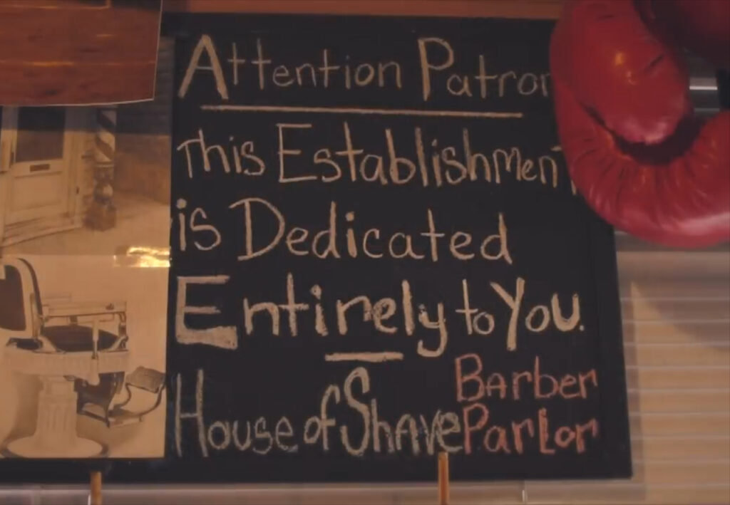 "Sign In The House Of Shave Barber Parlor reads, ""This establishment is dedicated entirely to you."""