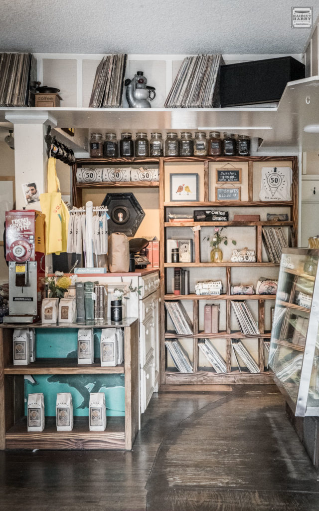 Shelves filled with coffee, books, and albums inside Pannikin coffee shop.
