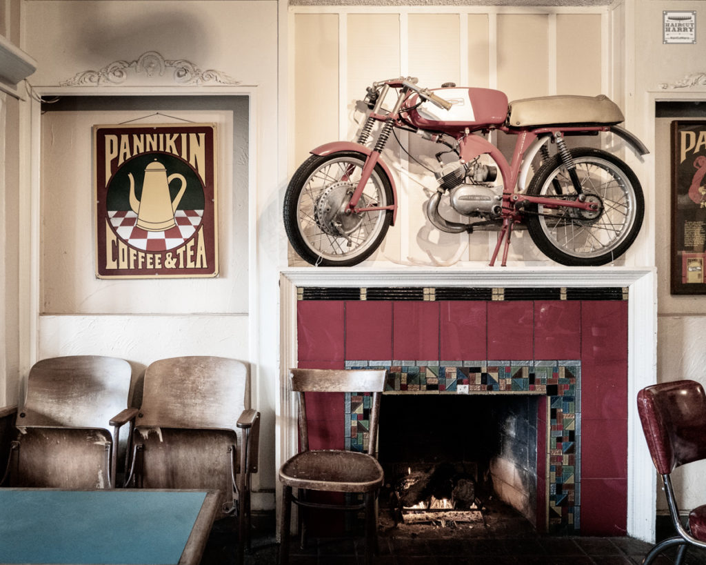 A bright red motorcycle can be found hanging above the open fireplace in the Pannikin coffee shop, San Diego