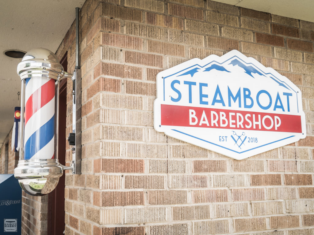 Barber pole and Steamboat Barbershop sign outside of the shop.