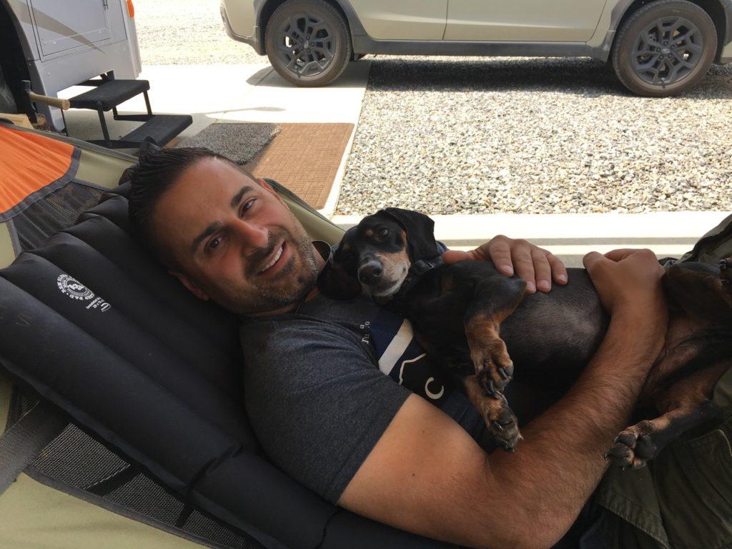 John sitting with their dachshund Buddy.