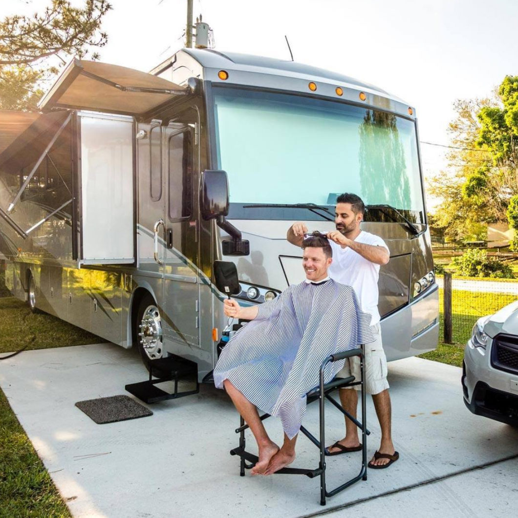 John cutting hair outside in front of their RV.