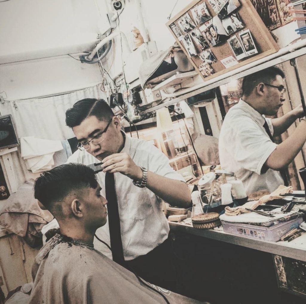 Mark giving a customer a haircut at Oi Kwan Barbers.