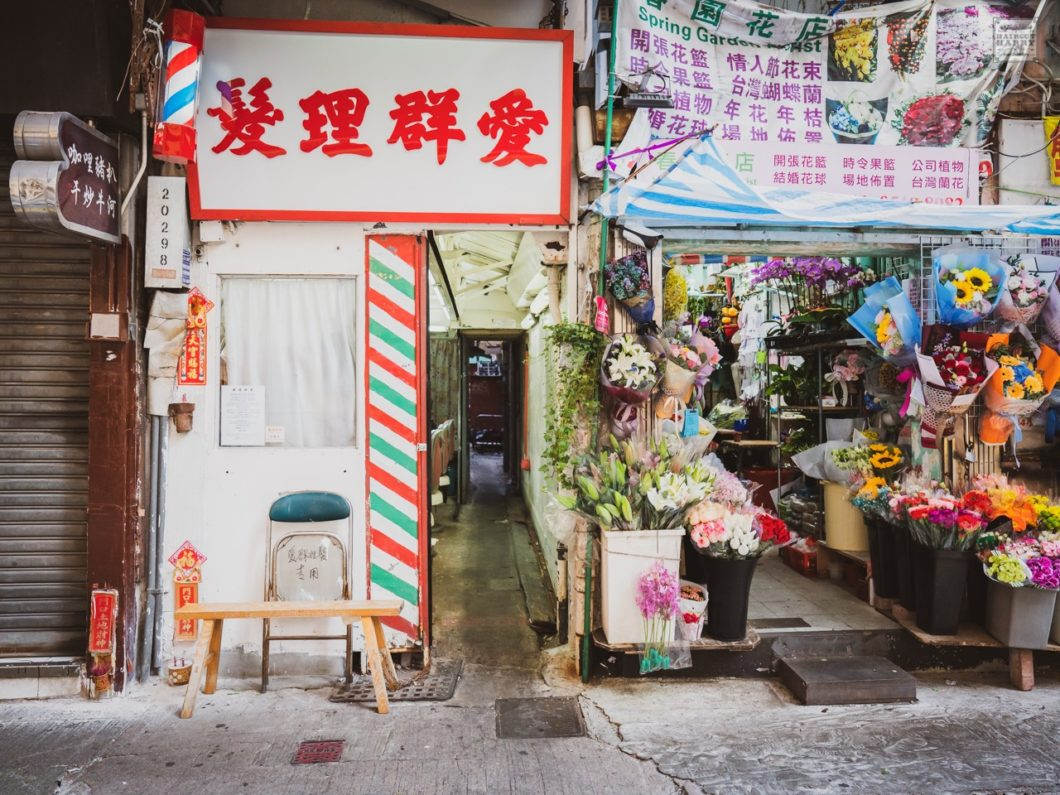 Oi Kwan Barbers is situated in between a flower shop and a busy local restaurant.