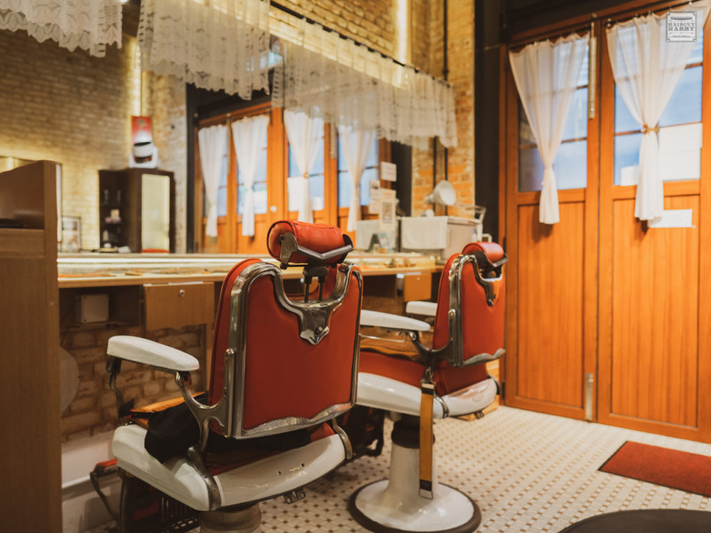 Inside the second Oi Kwan Barbers shop location red barber chairs await you.