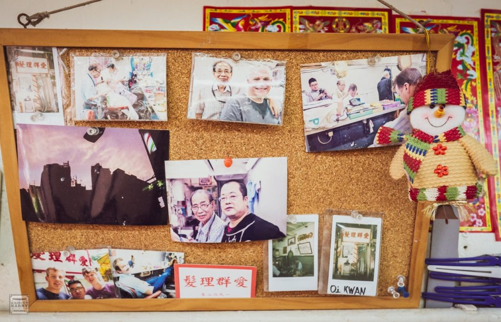 Photos of the barbershop are pinned to a bulletin board that hangs inside Oi Kwan Barbers.