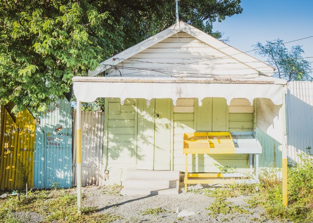 Green and yellow pastel colored traditional wooden Antiguan building.