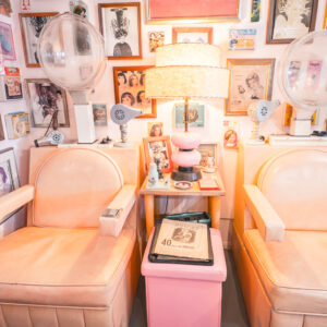 Vintage pastel colored beauty salon chairs against a wall of framed photos at the Beauty Bubble Salon