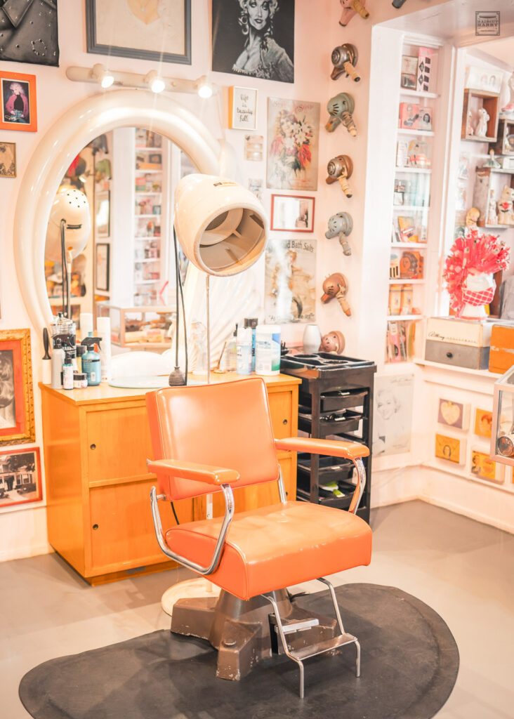 Orange salon chair inside the Beauty Bubble is surrounded by vintage beauty items on display