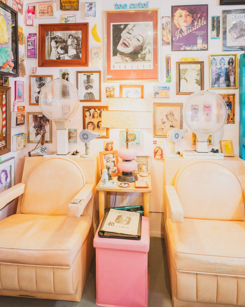 A pair of vintage 1960s pastel hair dryer chairs sit against a wall of framed pictures