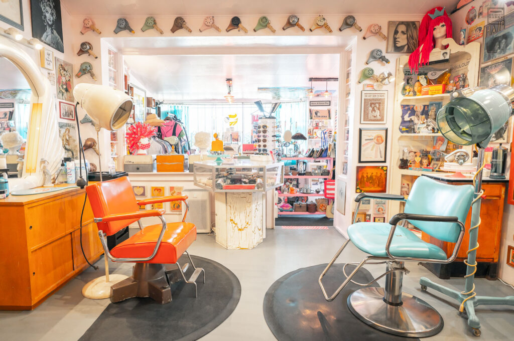 One orange and one turquoise salon chair sit inside the Beauty Bubble Salon and Museum