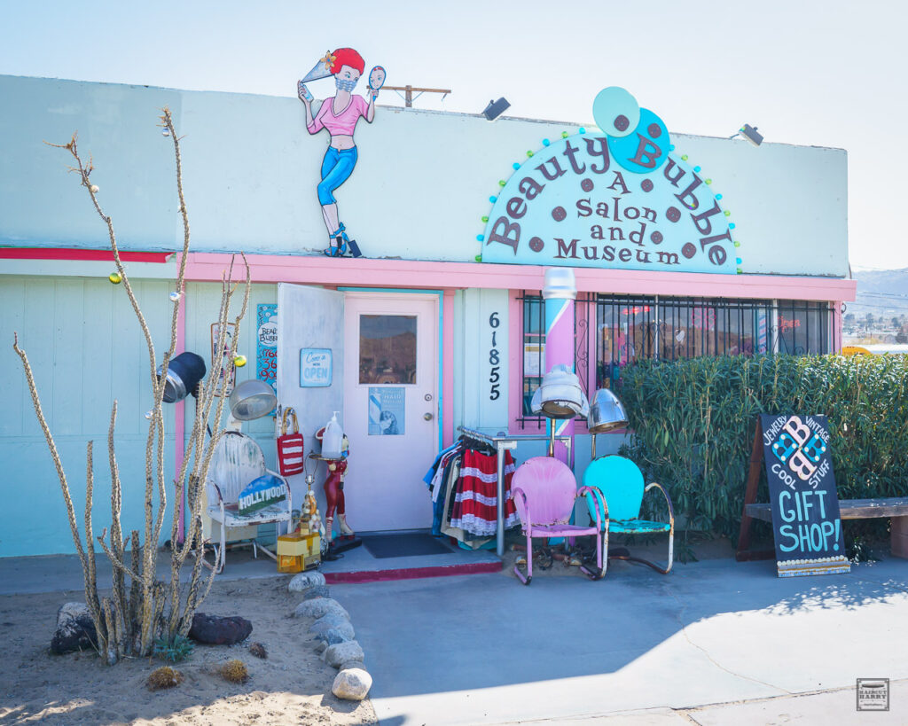 The pastel pink and blue exterior of the Beauty Bubble Salon and Museum is set against the Southern California desert landscape.