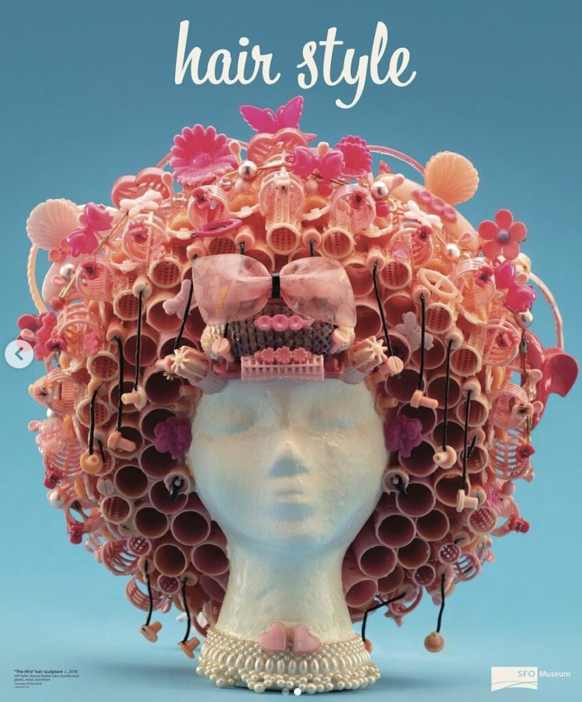 """The Afro"" hair sculpture created with pink rollers, clips, and barrettes is in the ""Hair Style"" exhibit at SFO Museum."