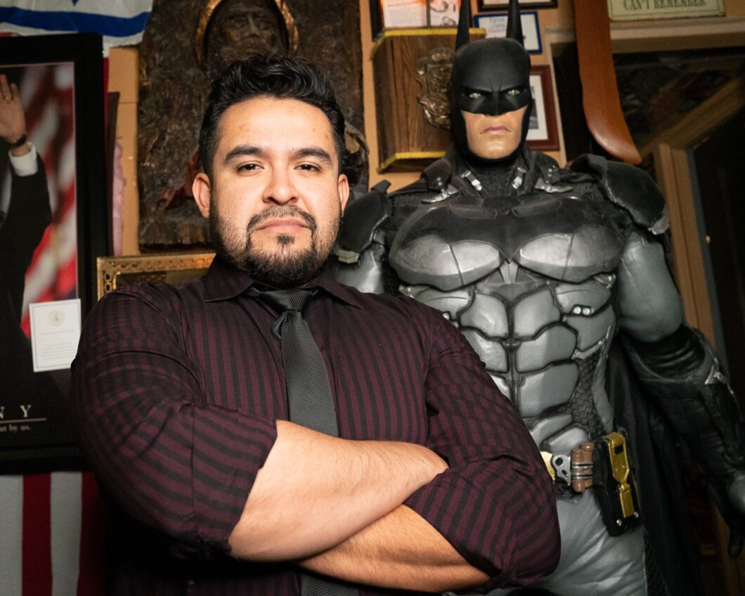 Matt standing with his life-size statue of Batman inside Matt's Barber Parlor