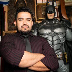 Matt standing with his life-size statue of Batman inside Matt's Barber Parlor