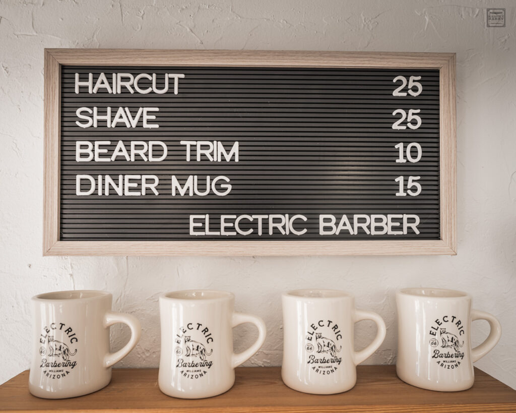 Four coffee mugs with the Electric Barbering logo are on display in the barbershop.