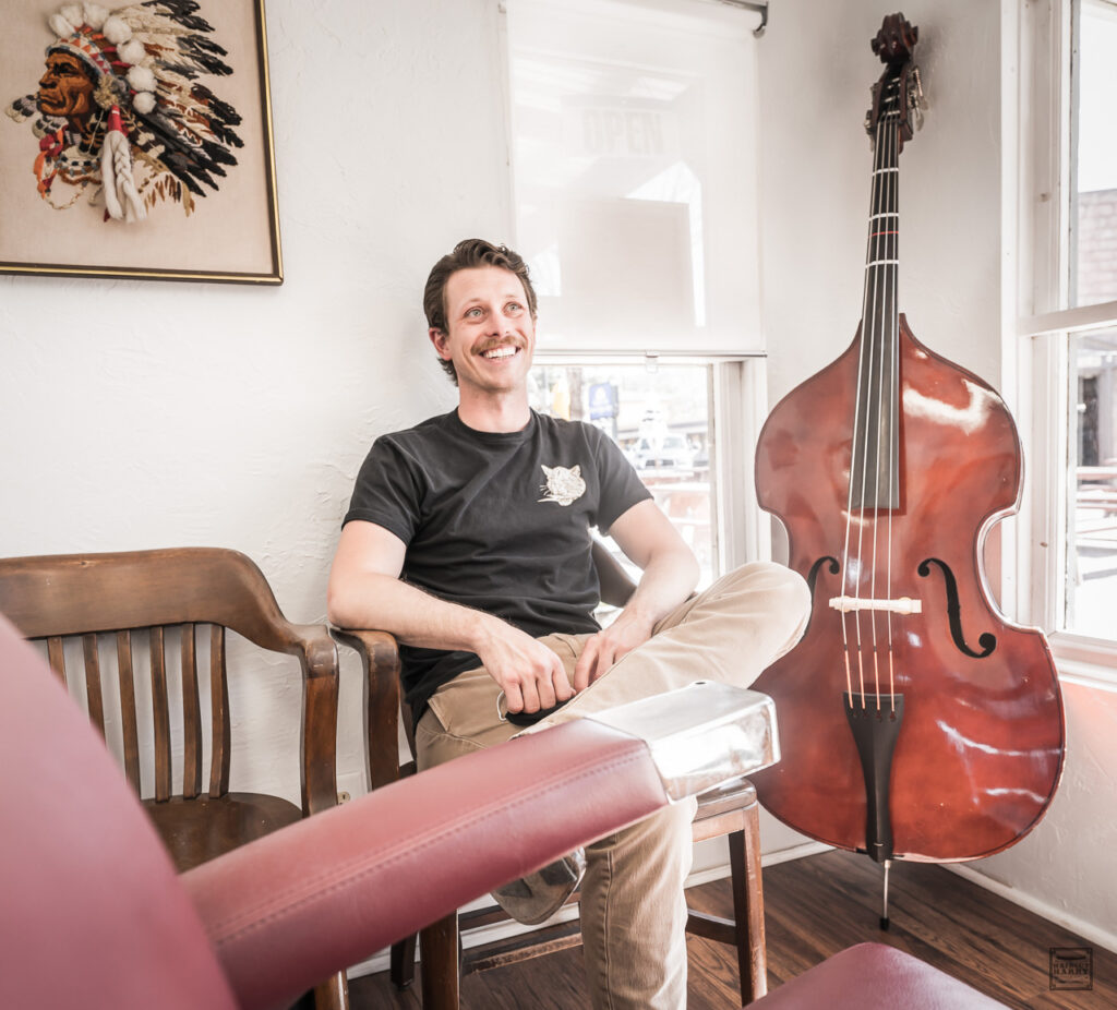 Calen sitting inside his barbershop next to his double bass.